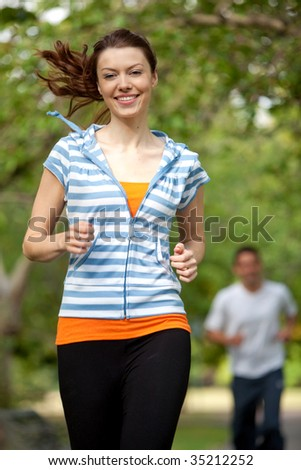Athletic woman running at the park smiling - stock photo