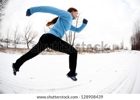 Athletic woman running in winter