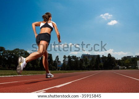 Athletic woman running on track - stock photo