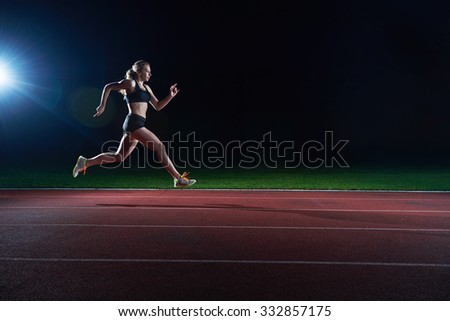 Athletic woman running onrace  track - stock photo