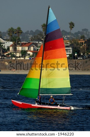 Athletic woman sailing in San Diego against a background of out-of-focus suburban houses...
