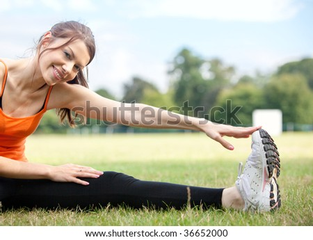 Athletic woman stretching her leg at the park - stock photo
