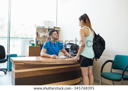 Athletic woman talking with fitness trainer at the gym - stock photo
