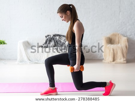 Athletic woman warming up doing weighted lunges with dumbbells workout exercise for butt legs at home healthy lifestyle sport bodybuilding concept. - stock photo