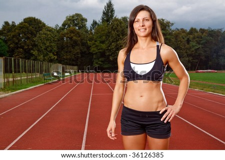 Athletic woman with a big smile on track - stock photo
