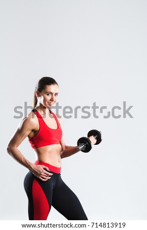 Athletic woman with dumbbell isolated on a white background.
