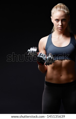 Athletic woman with dumbbells on a dark background - stock photo