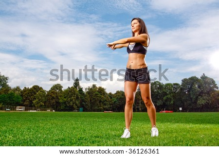 Athletic woman working out on field - stock photo