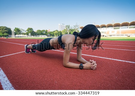 Athletic woman working out on track, plank position - stock photo
