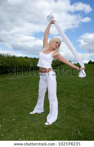 Athletic young blonde woman with a shapely body standing doing stretching exercises on a lush green lawn - stock photo