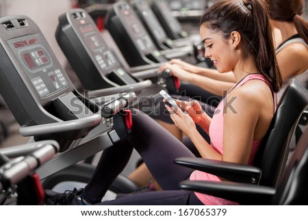 Athletic young brunette social networking and texting during a class at the gym - stock photo