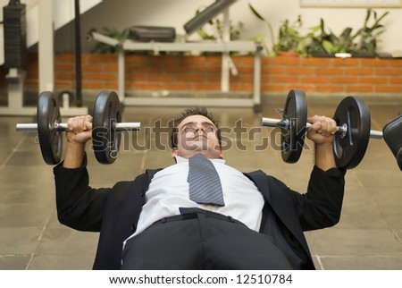 Athletic, young businessman bench pressing weights in a gym - stock photo