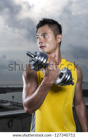 Athletic Young Chinese man exercising outdoors with dumbbells. Muscular Asian man exercising with weight training equipment. Male fitness concept. - stock photo