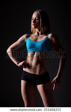 Athletic young girl on dark background.