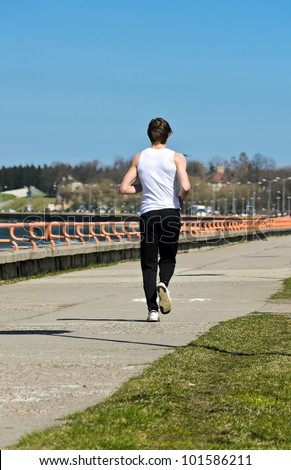Athletic young male running on the shoreline. From the back - stock photo