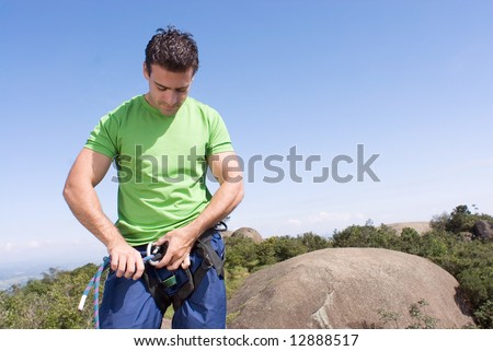 Athletic young man attaching a climbing rope to his climbing harness. Vertically framed shot against a clear blue sky - horizontally framed shot - stock photo