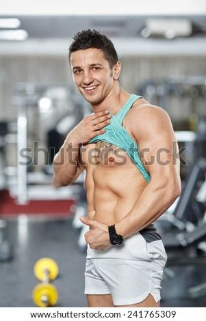 Athletic young man displaying well defined abs in the gym - stock photo
