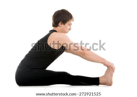 Athletic young man does yoga, pilates or fitness exercises, seated Forward Bend pose (Intense Dorsal Stretch), Paschimottanasana, stretching spine, shoulders, hamstrings - stock photo