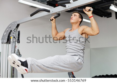 Athletic young man doing exercise on high bar.