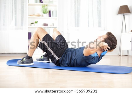 Athletic Young Man Doing Indoor sit Ups Exercise for Abdomen on Top of a Mat at Home. - stock photo