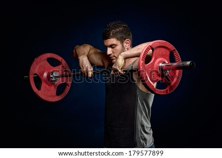 athletic young man exercising in the gym - stock photo