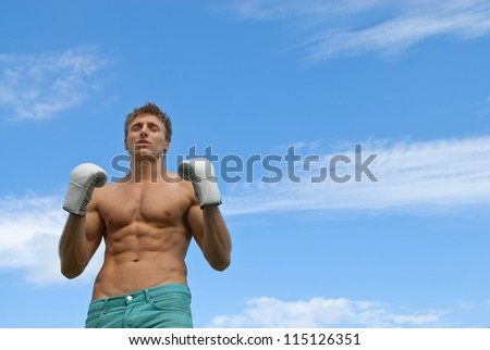 Athletic young man in boxing gloves, on blue sky background.