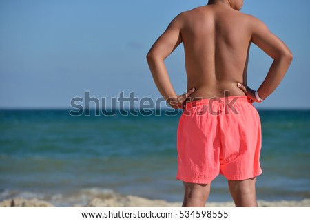 Athletic young man in pink shorts sits on the beach and looks at the sea, he prepares to go and swim. Burning sun, holiday