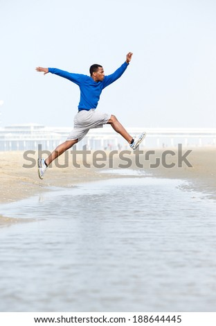 Athletic young man jumping over water at the beach
