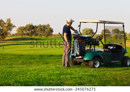 Athletic young man playing golf, choising club - stock photo