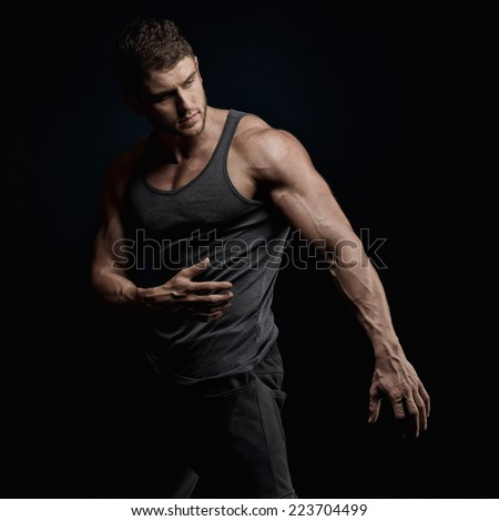 athletic young man portrait in studio with dark background