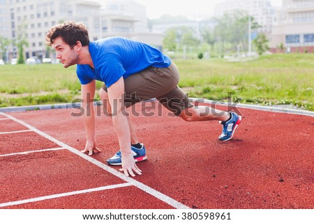 Athletic young man runner in steady position before run on a stadium running track preparing for training. Attractive male model in casual sportswear during workout on summer day - stock photo