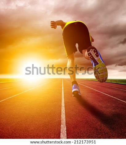 Athletic young man running on race track with sunset background - stock photo