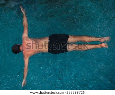 Athletic young man swimming in the pool - stock photo