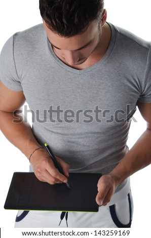 Athletic young man using digital graphic tablet to draw sketch - stock photo