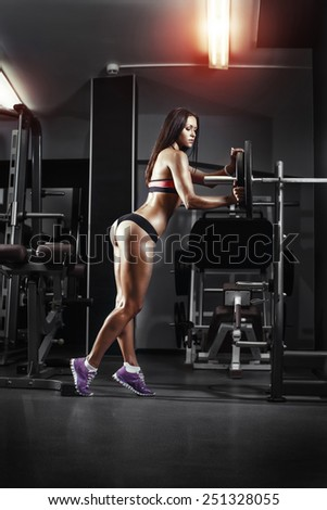 athletic young sexy girl sets weight on barbell in the gym - stock photo
