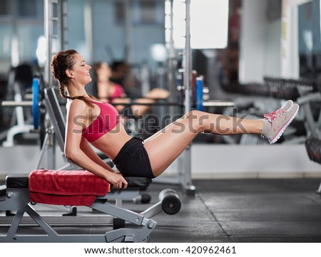 Athletic young woman at the gym doing abs crunches on a bench