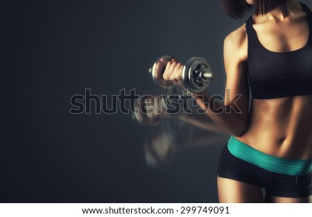 athletic young woman doing a fitness workout with dumbbells on black studio background - stock photo