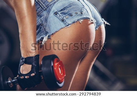 Athletic young woman doing a fitness workout with weights. buttocks close-up. - stock photo