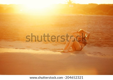 Athletic young woman doing abdominal crunch on the beach at beautiful orange sunset, athletic young girl doing exercises on the beach, fitness and healthy lifestyle concept - stock photo