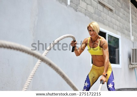 Athletic young woman doing some crossfit exercises with a rope outdoor - stock photo