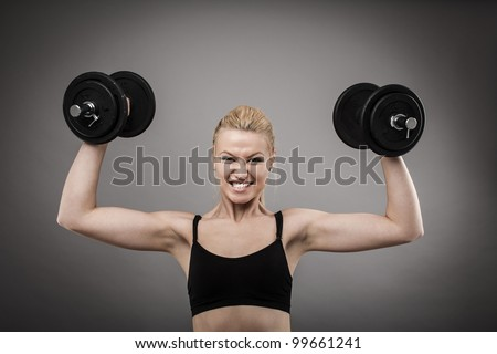 Athletic young woman doing workout with weights