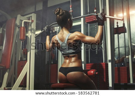 athletic young woman engaged in the simulator in the gym - stock photo