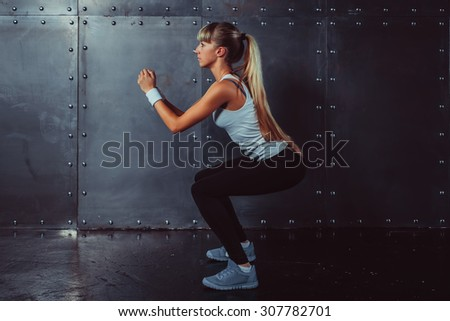 Athletic young woman fitness model warming up doing squats exercise for the buttocks concept sport slimming healthy lifestyle. - stock photo