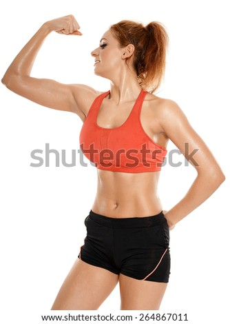 Athletic young woman flexing her biceps, studio shot - stock photo