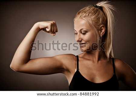 Athletic young woman flexing her biceps, studio shot