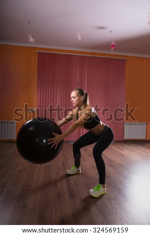Athletic Young Woman Holding Large Fitness Ball While Doing a Squatting Exercise Inside the Gym. - stock photo