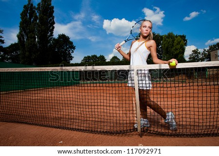 Athletic young woman in a tennis suit and racket in her hand standing behind the net - stock photo