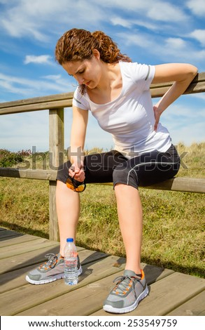 Athletic young woman in sportswear sitting touching her lower back muscles by painful injury, over a nature background. Sport injuries concept. - stock photo