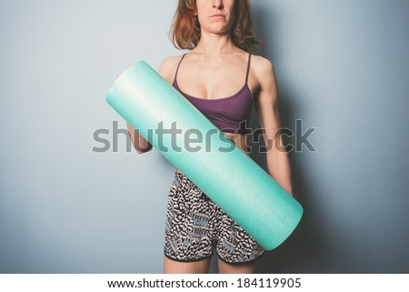 Athletic young woman is holding a foam roller for exercise - stock photo