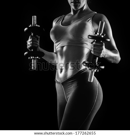 Athletic young woman lifting weights at the gym - stock photo